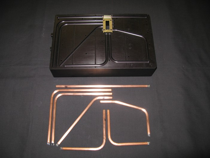Figure 1.  A HiK™ plate is fabricated by inserting flattened heat pipes into slots milled in aluminum (or other metals).  Heat pipes are used to spread heat from the gold-colored region to the rest of the box.
