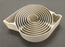 A 3D-printed Swiss-roll combustor (stainless steel), sectioned to show the internal structure.