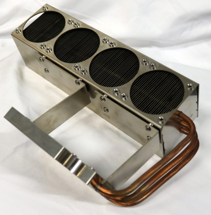 Block-Heat Pipe Fin Assembly.  The heat pipes transport heat from electronics mounted on the block  to a series of fins.  Fans mounted over the circular openings supply air to cool the fins.